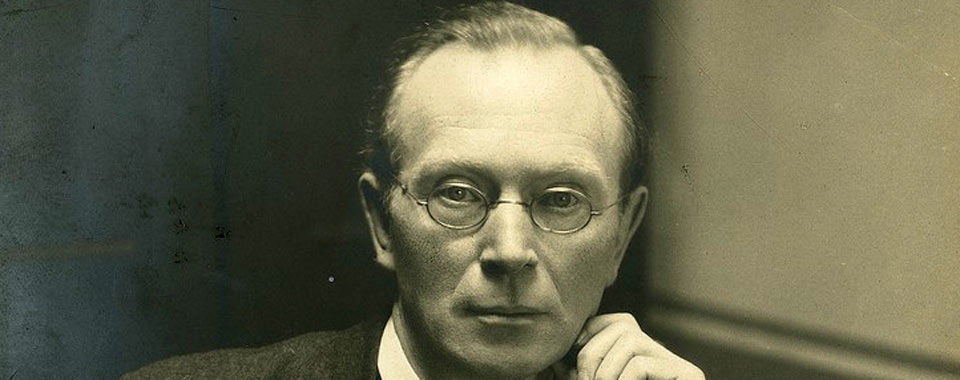 LA30/PH/325 Portrait photograph of Eoin MacNeill seated at a desk with an open book.